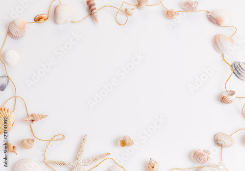 Romantic composition of exotic seashells, oyster, starfish on white background. Tropical summer vacation or Birthday, Wedding Day concept. Flat lay, top view. Marine design.