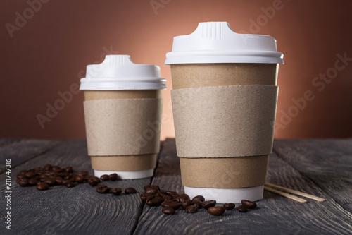Two single-use containers with lid for hot coffee, on wooden table