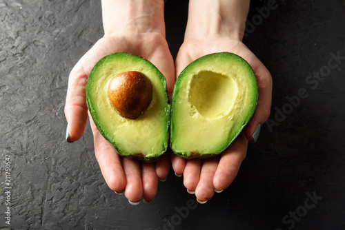Valokuvatapetti Fresh avocado fruit in girl hands