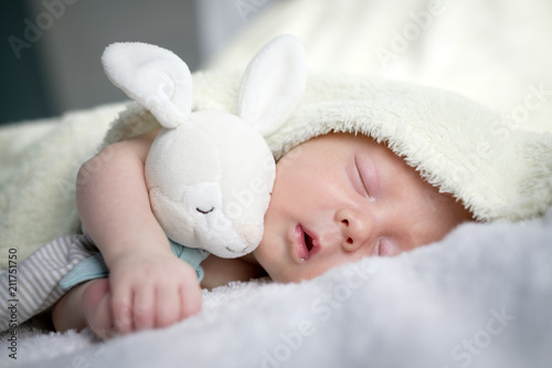 Fototapeta Newborn baby boy portrait on white carpet closeup. Motherhood and new life concept obraz