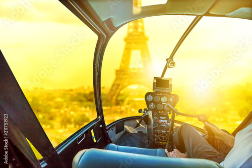 Poster Helicopter Helicopter cockpit interior flying on Tour Eiffel at sunset in Paris, France. Travel and tourism concept. Scenic flight above Paris skyline. Urban sunset aerial scene on blurred background.