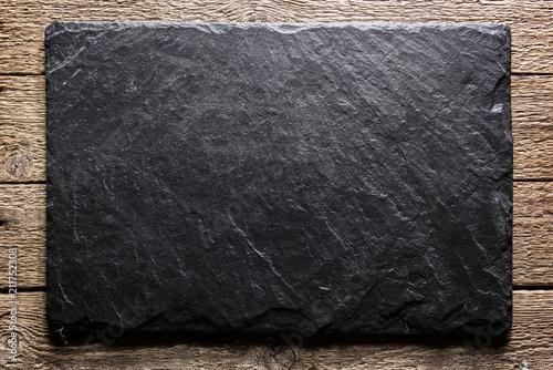 Obraz na plátně Black slate board on grunge wooden table closeup
