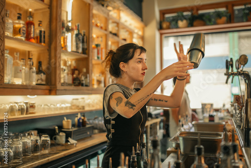 Photo Young female bartender mixing cocktails behind a bar counter