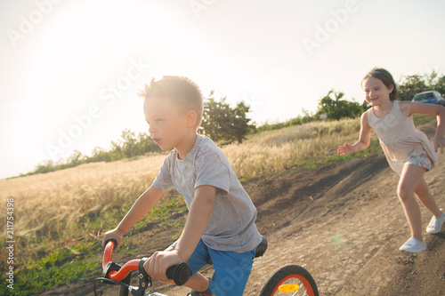 Boy and girl in the field. The boy is riding a bicycle, and the girl is running alongside. A cheerful, happy childhood in the village.