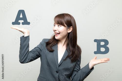 Fotografía  AとBを比べる女性