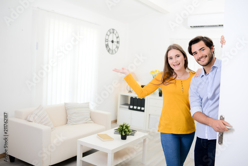 cheerful young couple man and woman welcome friends at open front door new stude Fototapeta