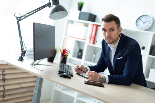 A young man stands near a table in the office, holds a pencil in his hand and works with documents and a computer.