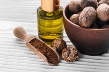 Nutmeg Essential Oil On A Gray Wooden Background