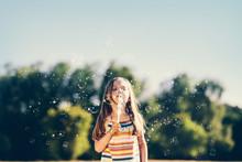 Little Girl Blowing Soap Bubbl...