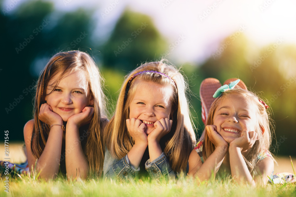 Fototapeta Three smiling little girls laying on the grass in the park.