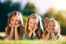 Three Smiling Little Girls Laying On The Grass In The Park.
