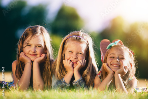 Staande foto Wanddecoratie met eigen foto Three smiling little girls laying on the grass in the park.