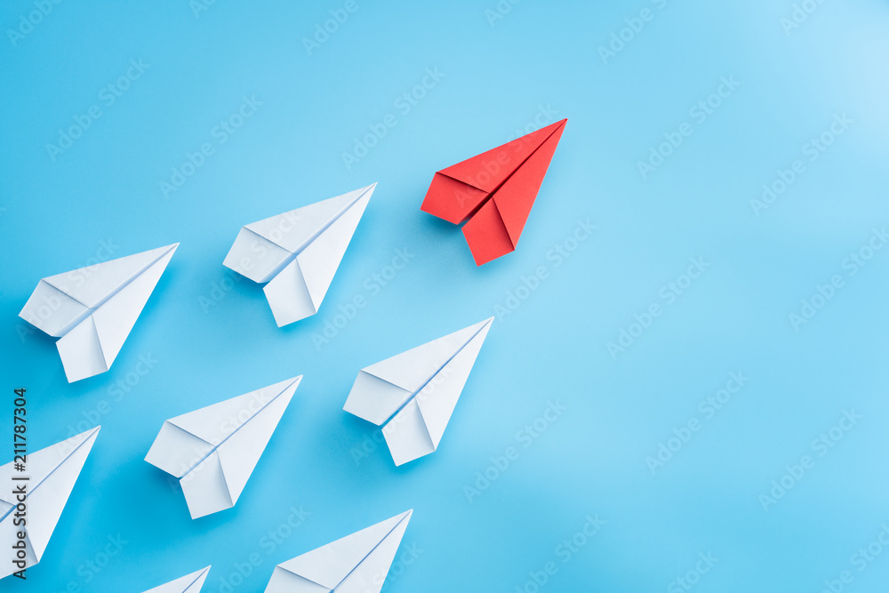 Fototapeta Leadership concept with red paper plane leading among white on blue background