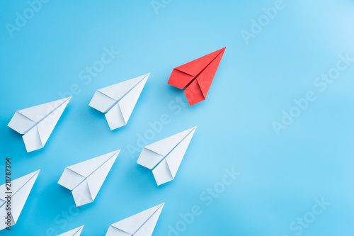 Fotografía  Leadership concept with red paper plane leading among white on blue background