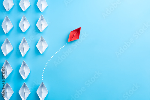 Obraz Group of white paper ship in one direction and one red paper ship pointing in different way on blue background. Business for innovative solution concept. - fototapety do salonu
