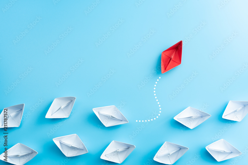 Fototapety, obrazy: Group of white paper ship in one direction and one red paper ship pointing in different way on blue background. Business for innovative solution concept.