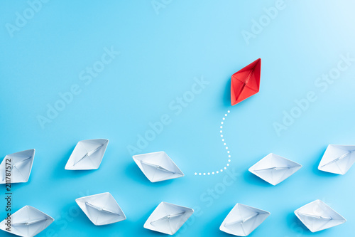 Fotografía  Group of white paper ship in one direction and one red paper ship pointing in different way on blue background