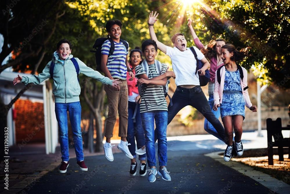 Fototapeta Smiling school kids having fun on road in campus
