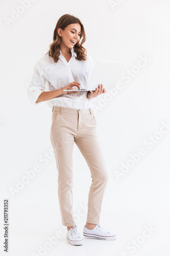 Obraz Portrait of adorable smiling woman with long brown hair holding and looking at silver laptop, isolated over white background in studio - fototapety do salonu