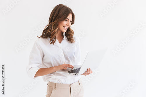 Staande foto Wanddecoratie met eigen foto Portrait of adorable smiling woman with long brown hair holding and looking at silver laptop, isolated over white background in studio