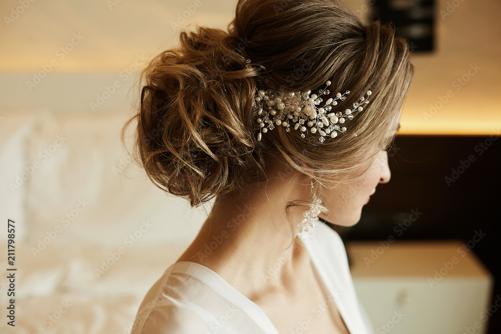 Fototapeta Wedding hairstyle of beautiful and fashionable brown-haired model girl in a lace dress, with earrings and jewelry in her hair