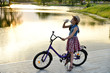 A child with a Bicycle stands on the river Bank at sunset and drinks water from a transparent bottle. Portrait. Landscape orientation