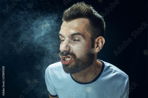 Leinwand Poster  Young handsome man with beard sneezing, studio portrait