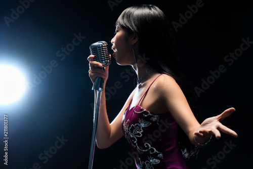Fotografia Asian woman singer holding a microphone singing.