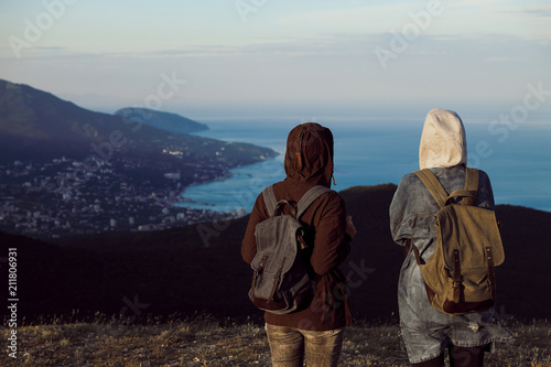 Photo  Two girls traveler stand on the top of the mountain, look down, jump, rejoice and dance