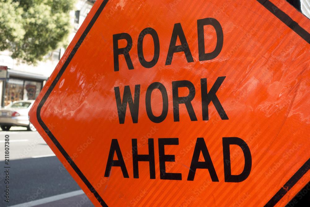 Fototapeta diamond shaped orange red reflector street sign that reads road work ahead