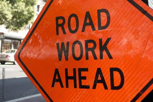 diamond shaped orange red reflector street sign that reads road work ahead Fototapeta