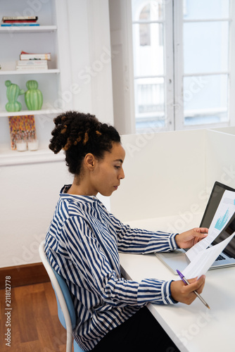 Woman sitting at a desk looking a documents