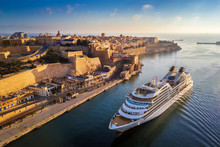 Valletta, Malta - Cruise Ship Sailing Into Grand Harbor At Sunrise With The Ancient City Of Valletta At Background