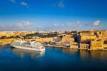 Valletta, Malta - Cruise Ship In The Grand Harbor At Sunrise With The Ancient City Of Valletta At Background
