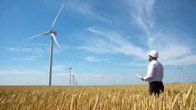 Worker Of A Wind Power Plant In A Yellow Wheat Field