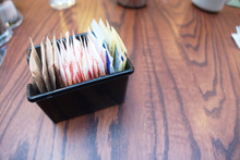 Various Single Serving Sugar Mini Bags On A Morning Table Coffe Shop