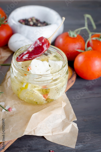 piece of soft cheese on the board and Marinated spicy  feta in a jar and  tomatoes for salad.