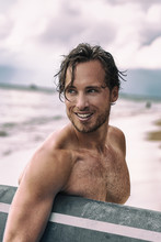 Sexy Young Man Surfer Beach Lifestyle. Smiling Male Beauty Model Tanned Relaxing Holding Surf Board On Tropical Vacation. Healthy Skin Care Portrait Concept.