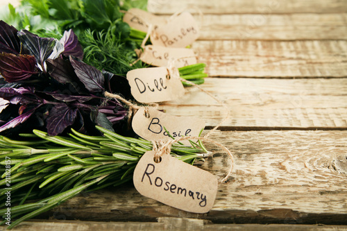 Poster Aromatische Different fresh herbs on brown wooden table