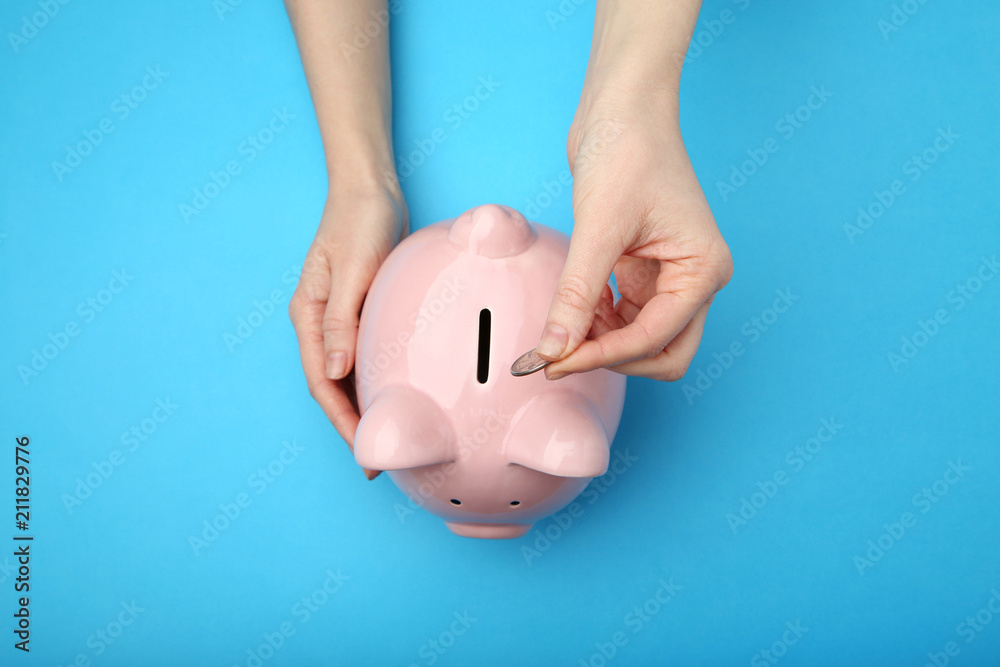 Fototapety, obrazy: Female hand putting coin into piggy bank on blue background