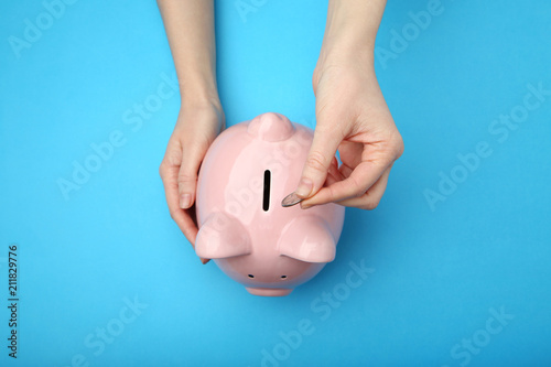 Fotografía  Female hand putting coin into piggy bank on blue background