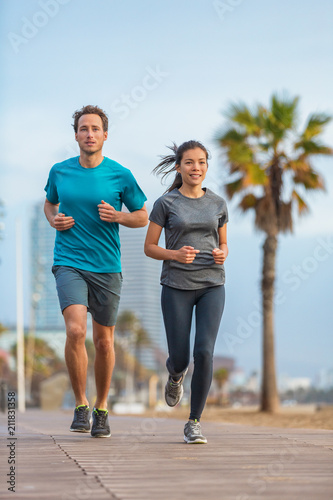 d193ded4d0bd2 Running couple runners friends jogging on Barcelona Beach, Barceloneta.  Healthy lifestyle young fit people training outside on boardwalk.