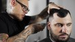 Tattoed barber makes haircut for customer at the barber shop by using hairclipper, mans haircut and shaving at the hairdresser, barber shop