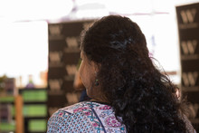 Beautiful Woman With Long Black Curly Hair Sits At A Meeting Or Lecture Indoors. She Listens And Watches Attentively. View From Her Back. Concept: Education &  Business.