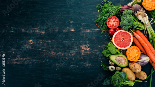 Healthy food. Vegetables and fruits. On a black wooden background. Top view. Copy space. - 211835916