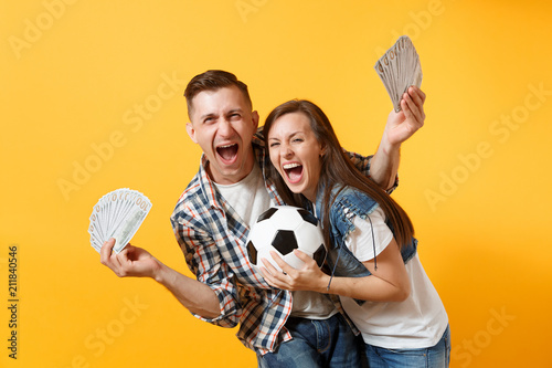 Young win couple, woman man, football fans holding bundle of dollars, cash money, soccer ball, cheer up support team isolated on yellow background Canvas Print