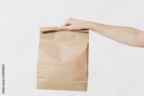 Fotografering Close up female holds in hand brown clear empty blank craft paper bag for takeaway isolated on white background