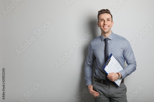Foto Male real estate agent with clipboard on grey background