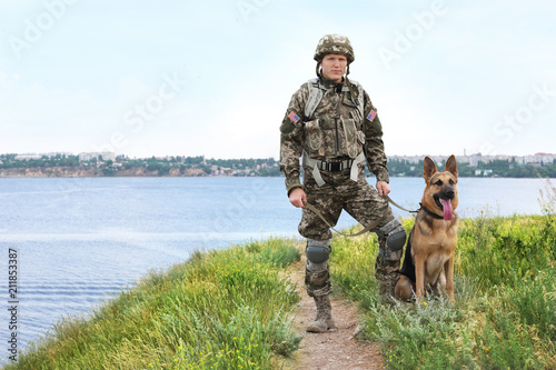 Fotografía  Man in military uniform with German shepherd dog near river