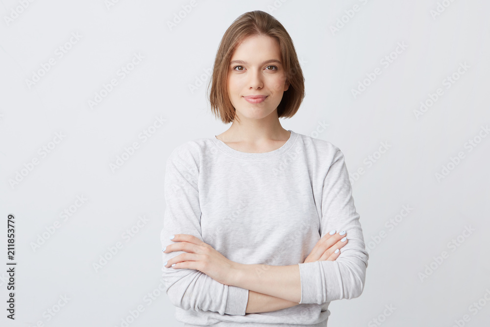 Fototapeta Closeup of happy pretty young woman in longsleeve standing with hands folded and looking directly in camera isolated over white wall Feeling confident